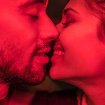 Young man kissing smiling woman