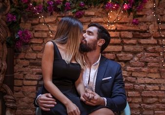 Young man kissing with blond woman on chair