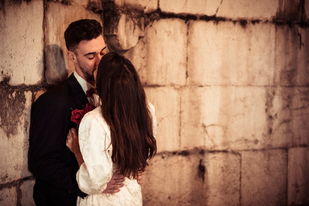 Young man kissing woman leaning on building wall
