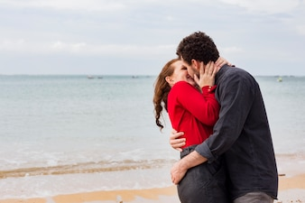 Young man kissing woman on sea shore