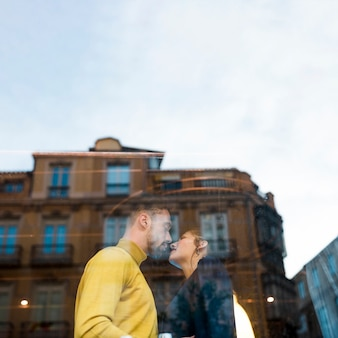 Young man kissing woman other side of window