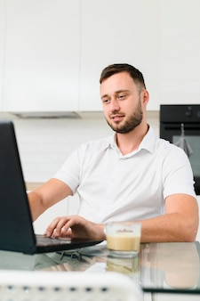 Young man in kitchen working on laptop