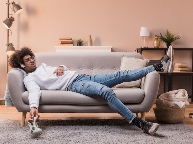 Young man laid on couch playing