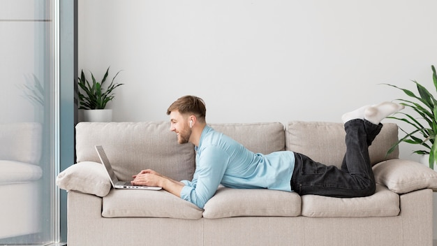 Young man laid on couch with laptop