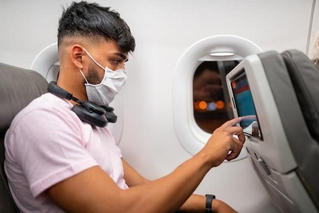 飛行機で旅行、保護フェイスマスクを身に着けている若い男ラテンアメリカ人