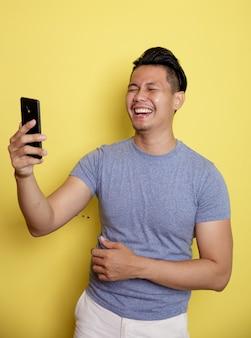 若い男は黄色の壁に隔離された電話を見ながら幸せに笑う