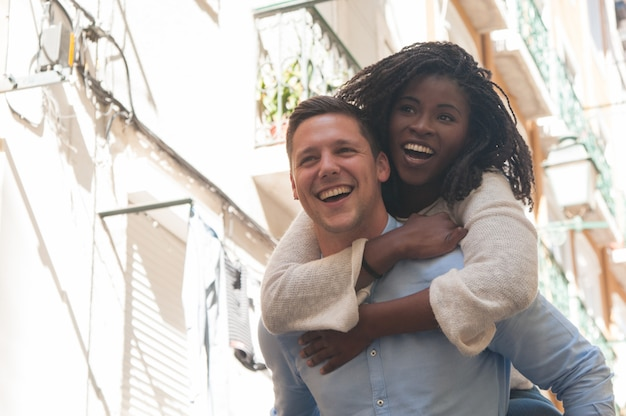 Young man laughing and carrying girlfriend on back outdoors