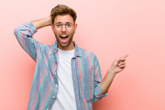 Young man laughing, looking happy, positive and surprised, realizing a great idea pointing to lateral copy space against pink wall