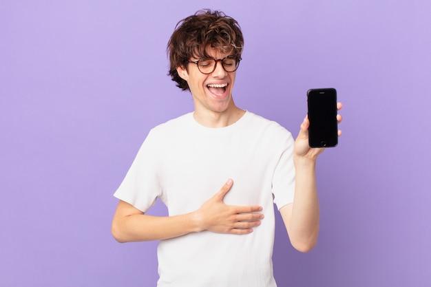 陽気な冗談で大声で笑い、独房を持っている若い男
