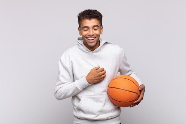 若い男は、いくつかの陽気な冗談で大声で笑い、幸せで陽気に感じ、楽しんでいます。バスケットコンセプト