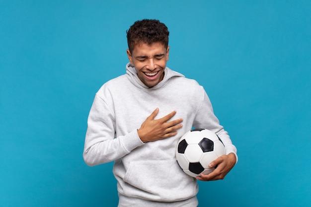 젊은 남자가 웃기는 농담에 큰 소리로 웃고, 행복하고 쾌활한 느낌, 재미. 축구 개념