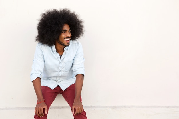 Young man laughing with hands on knees and afro
