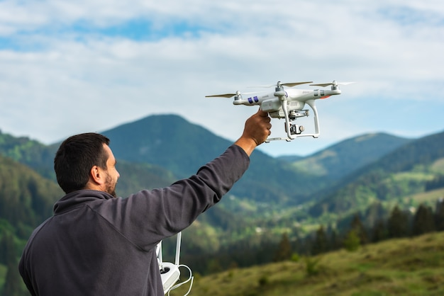 Young man launches a quadrocopter in the sky on the nature in the mountains