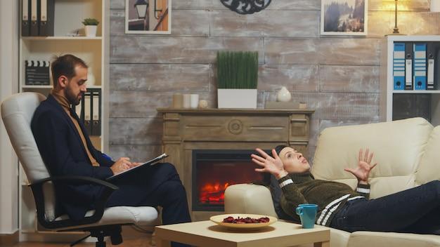 心理学者と話しているカップル療法でソファに横たわっている若い男。
