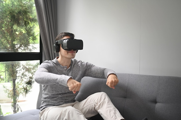 バーチャルリアリティメガネでビデオゲームを敷設する若い男。