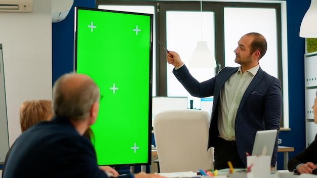 다양한 팀 브레인스토밍 앞에서 녹색 화면 모형 디스플레이를 사용하여 재무 전략을 제시하는 회사의 젊은 리더. 크로마 키 데스크탑이 있는 모니터를 보여주는 프로젝트 설명 관리자