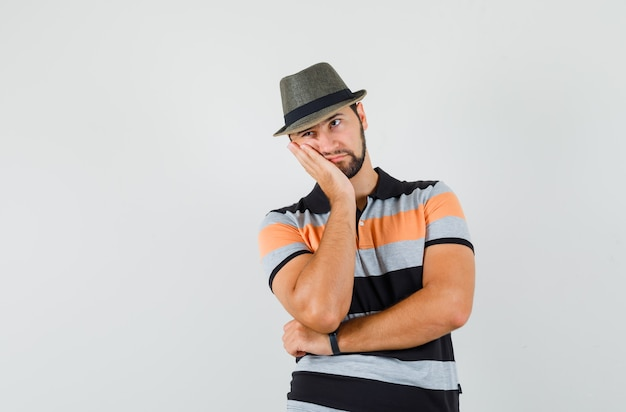 Young man leaning cheek on raised palm in t-shirt, hat and looking fatigued , front view.