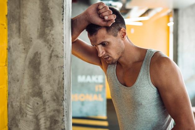 Молодой человек, опираясь на столбец в тренажерном зале