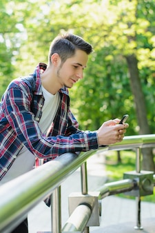Young man leaning on railings holding smartphone