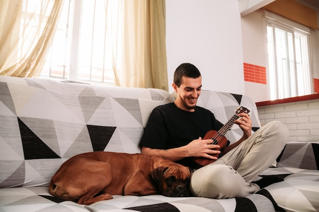 Young man learning to play the ukulele from his couch with her dog