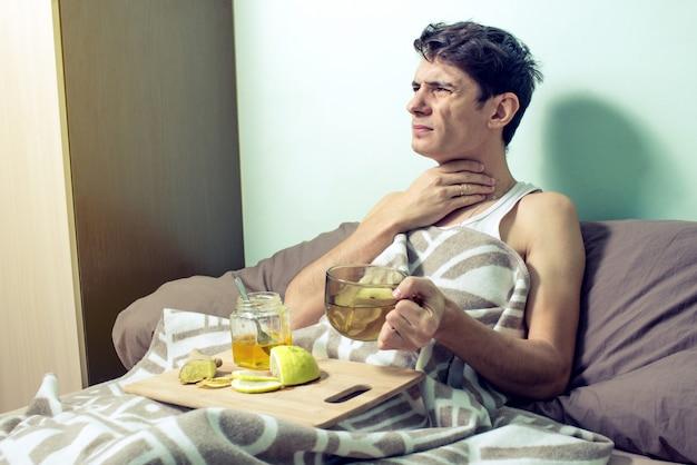 Молодой человек лежит в постели больной простудой и гриппом