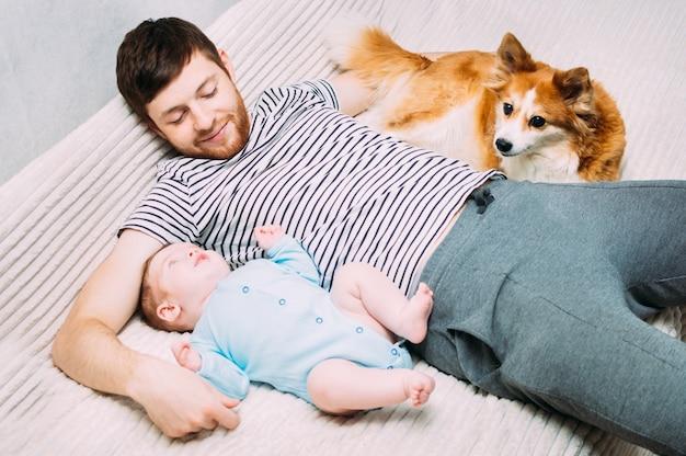 젊은 남자는 아이와 그의 개와 함께 침대에 누워 있습니다. 미소, 행복, 웃음, 휴식. 어린이 및 애완 동물 개념