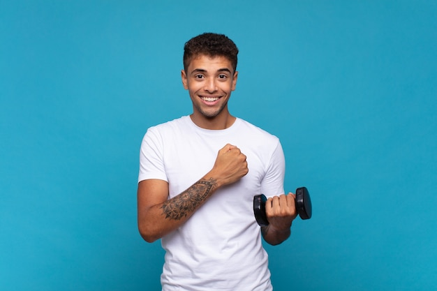 Young man lifting a sumbbell feeling happy, positive and successful, motivated when facing a challenge or celebrating good results