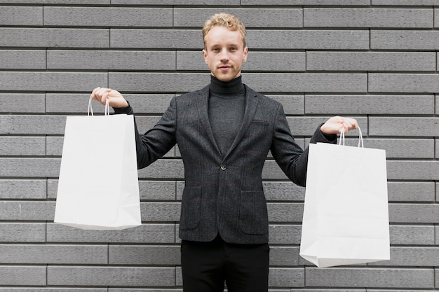 Young man lifting up the shopping bags