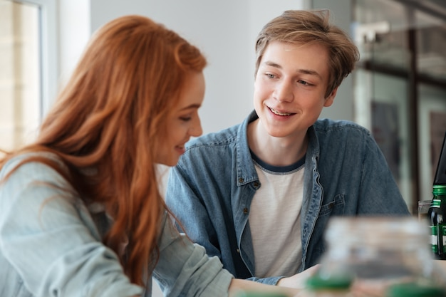 若い男がカフェで彼の友人を聞いて