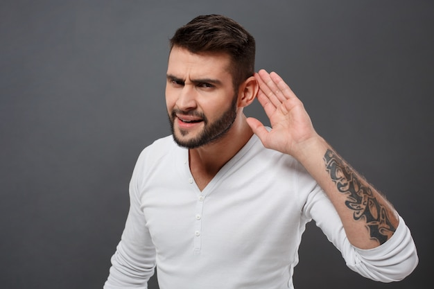 Young man listening holding hand near ear over grey wall