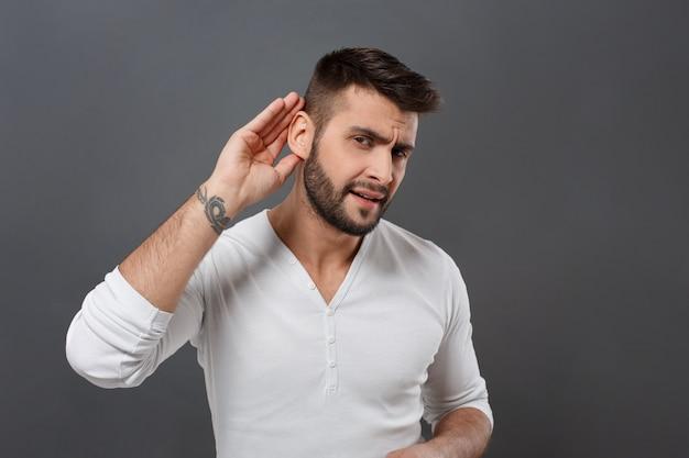 灰色の壁の上の耳の近くの手を握って聞いて若い男