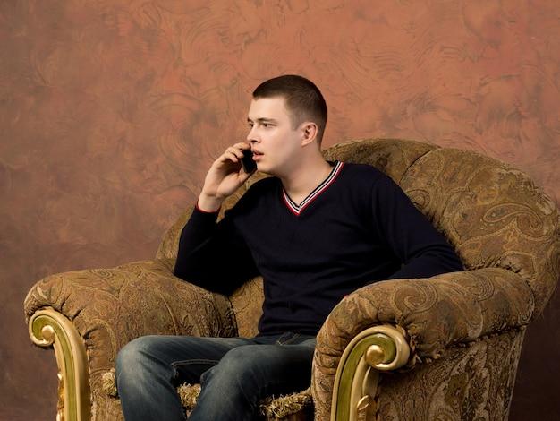 携帯電話での電話にショックを受けて聞いている若い男