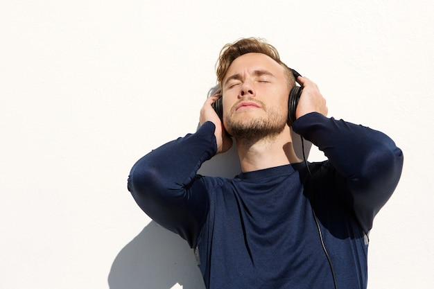 Young man listening to msuic with headphones