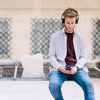 Young man listening music at outdoors