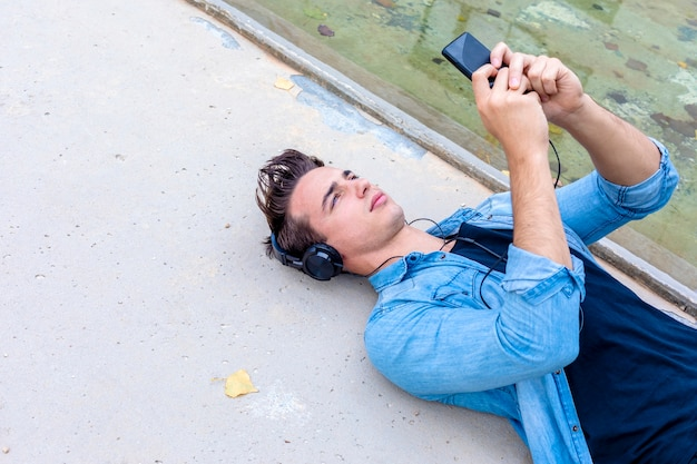 Young man listening music by smartphone lying down w