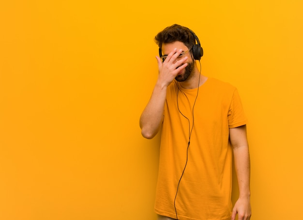 Young man listening to music embarrassed and laughing at the same time