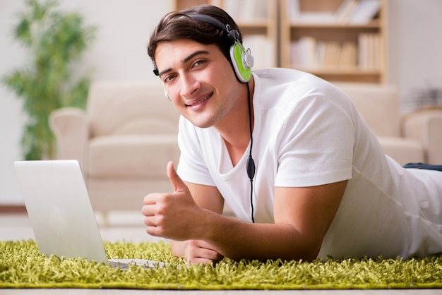 Young man listening to the music from laptop