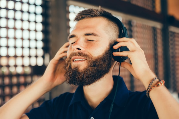 Young man listening music in headphones, using smartphone, outdoor hipster portrait
