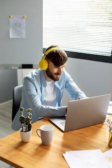 Giovane che ascolta musica con le cuffie mentre lavora