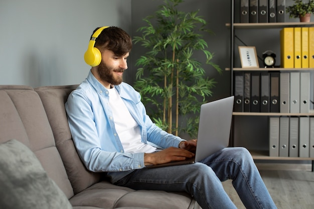 Young man listening to music on headphones while working