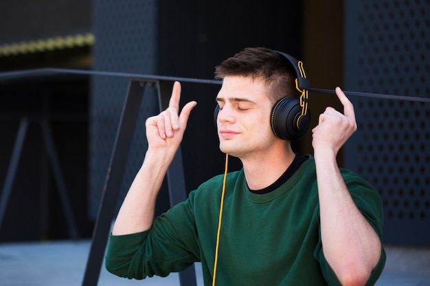 Young man listening to music in headphones with raised hands