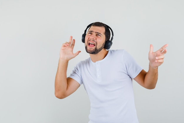 Молодой человек слушает музыку в белой футболке и выглядит энергичным. передний план.