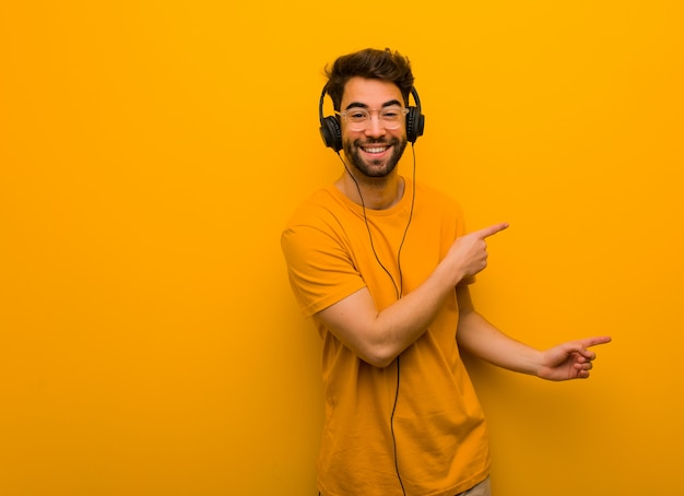 Young man listening to music pointing to the side with finger