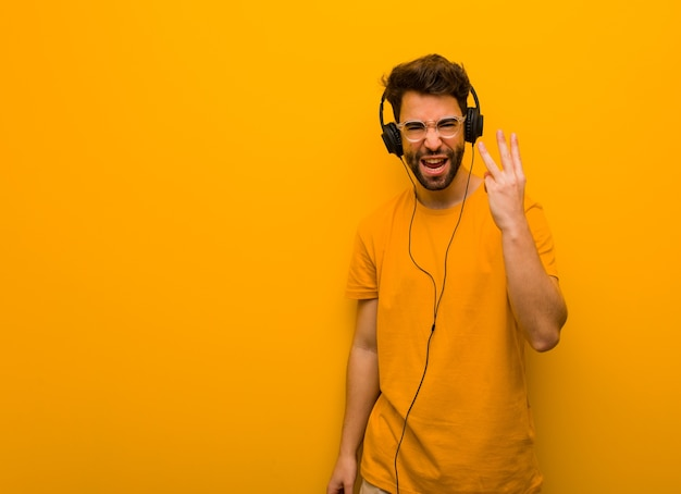 Young man listening to music showing number three