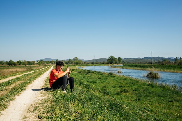 Young man listening music siting in bank of river