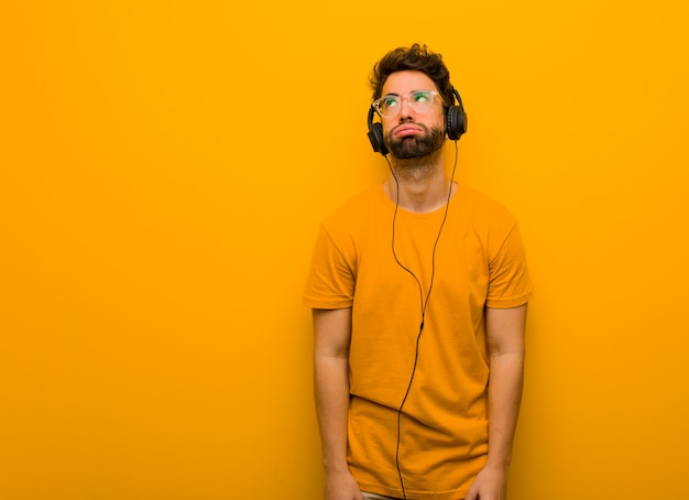 Young man listening to music tired and bored
