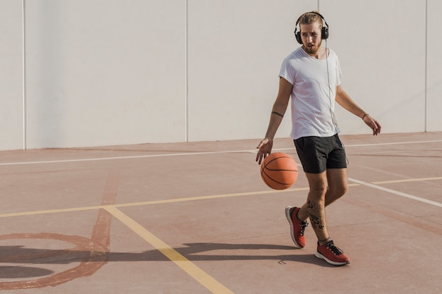 Young man listening to music while playing basketball in court