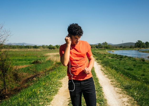 Young man listening music while walking on natural trail
