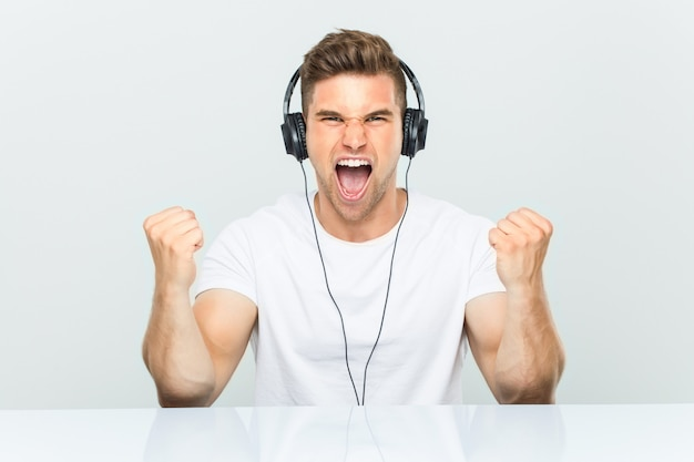 Young man listening to music with headphones cheering carefree and excited