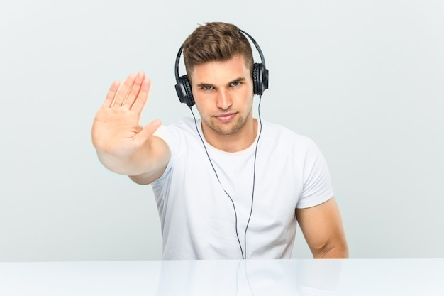 Young man listening to music with headphones standing with outstretched hand showing stop sign, preventing you.